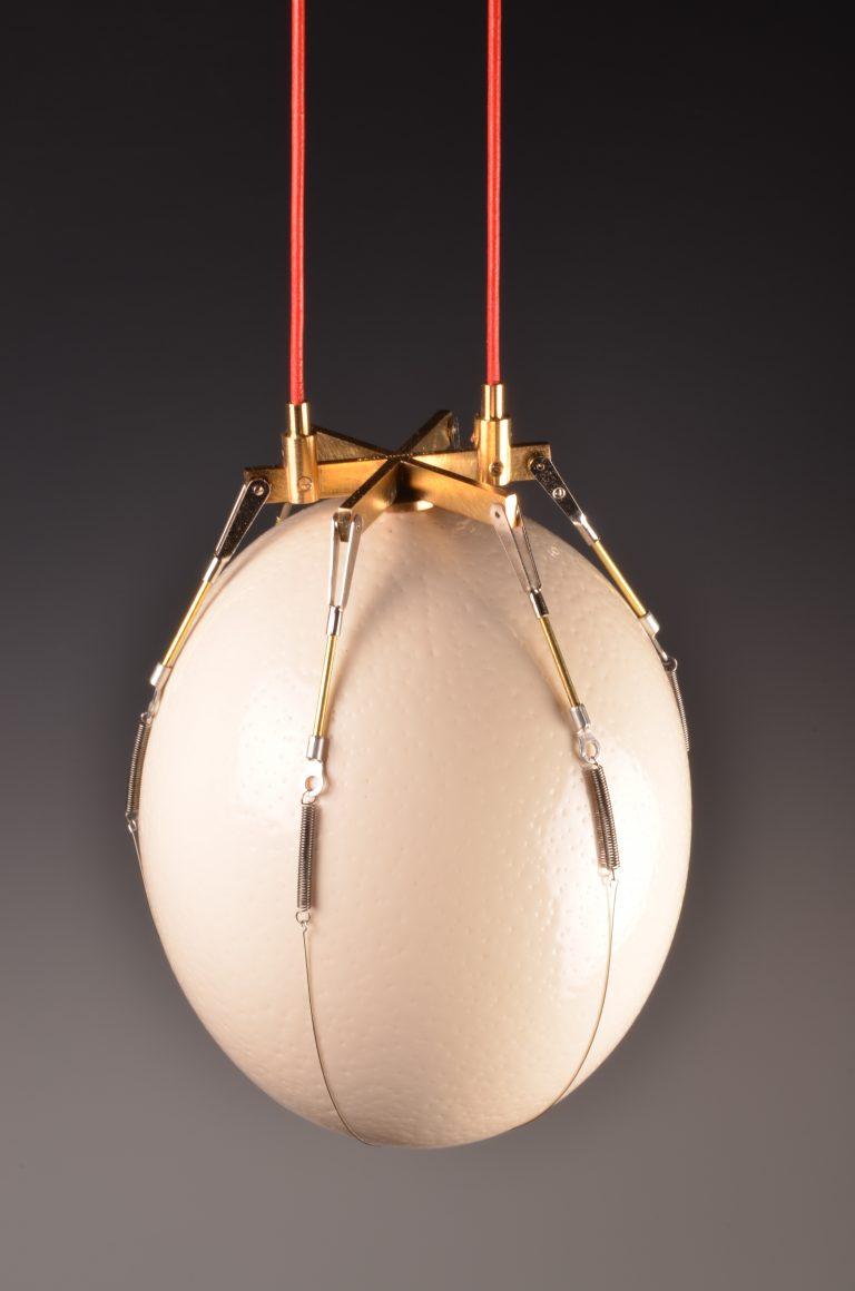 Sørlandets Kunstmuseum. Kunstsilo. Sigurd Bronger, Bæreinstrument for strutseegg / Wearable Device for Ostrich Egg, 2012. ostrich egg, gilded brass, leather string and rubber