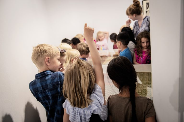 Barn i utstillingsrommet som rekker opp hånden